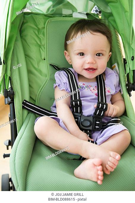 Mixed race baby sitting in stroller