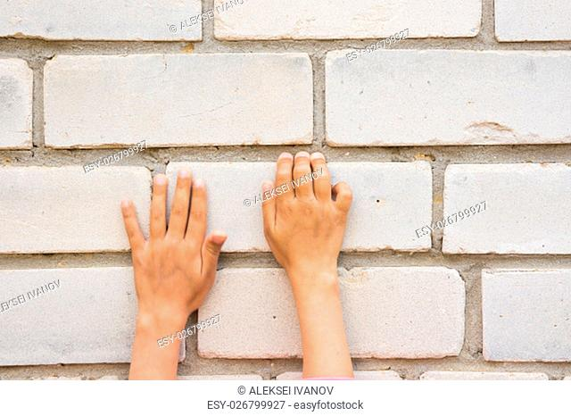 Children's hand trying to grab the tabs brick wall