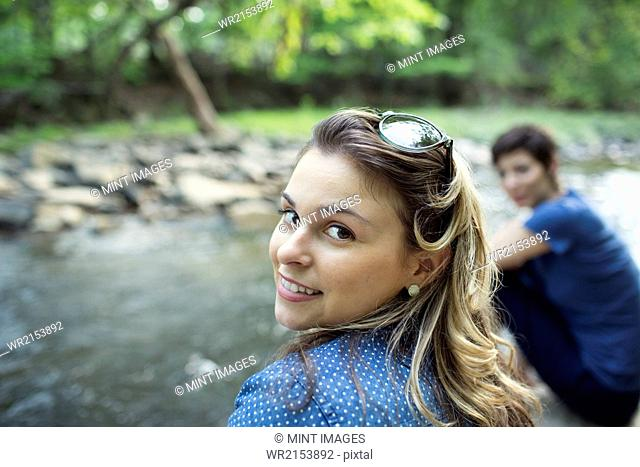 Two women sitting by a river bank looking over their shoulders