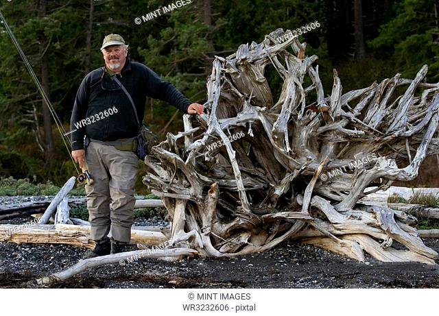 A portrait of a senior Caucasian male fly fisherman standing on a salt water beach next to a driftwood weathered root ball from an evergreen tree