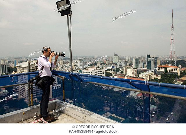 A man taking a photograph of the skyline in Ho Chi Minh City, Vietnam, 31 October 2016. Photo: Gregor Fischer/dpa   usage worldwide