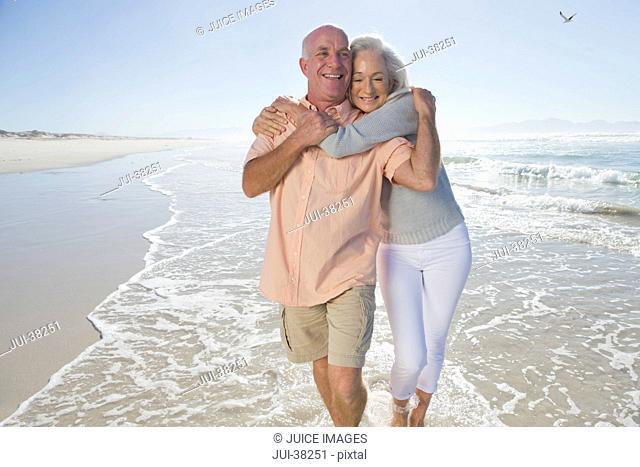 Happy senior couple hugging and walking on sunny beach