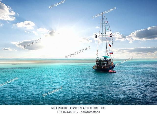 Yacht in the sea near island at sunrise