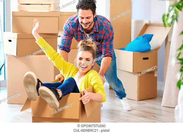Young couple in new home, woman sitting in cardboard box, man pushing her along, laughing