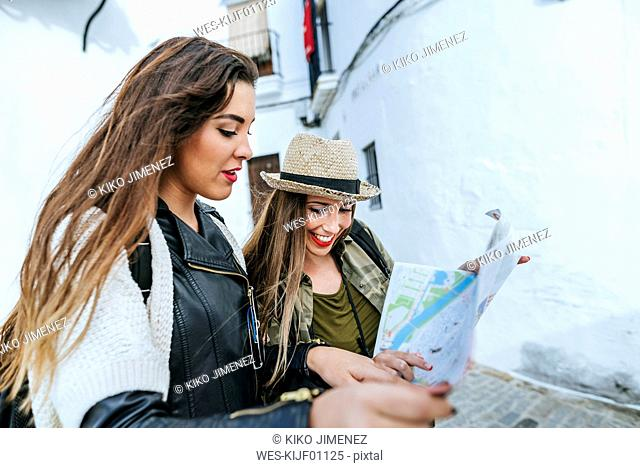 Two young women in a town looking at a map