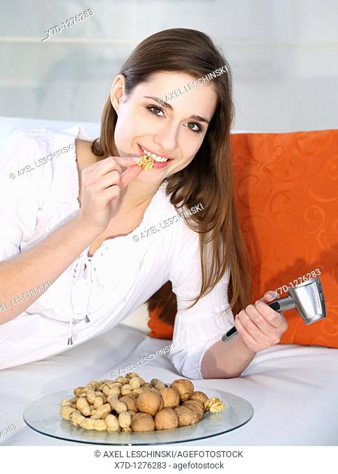 young brunette woman eating nuts