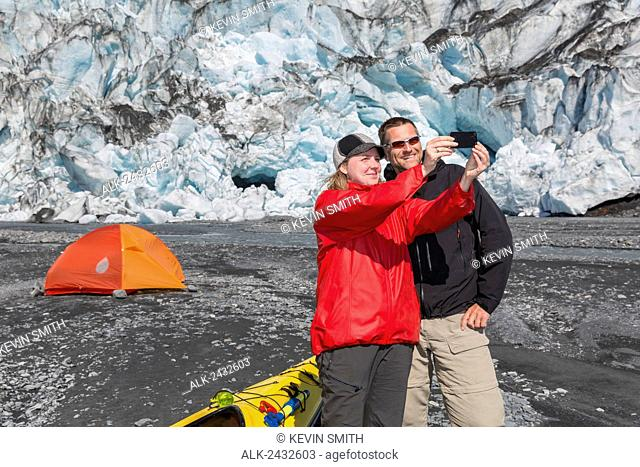 Couple take a Selfie at their camp in front of Shoup Glacier, Shoup Bay State Marine Park, Prince William Sound, Valdez, Southcentral Alaska