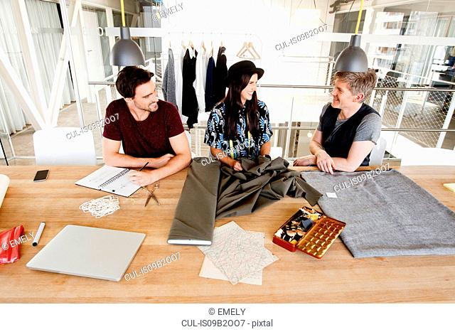 Fashion designers at desk discussing fabric smiling