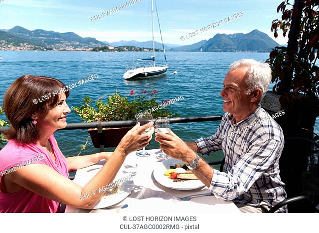 Older couple toasting with wine outdoors