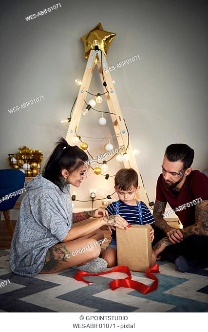 Boy opening Christmas present with his parents at home