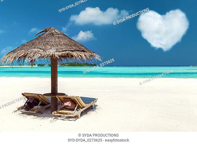 two sunbeds under palapa on maldives beach