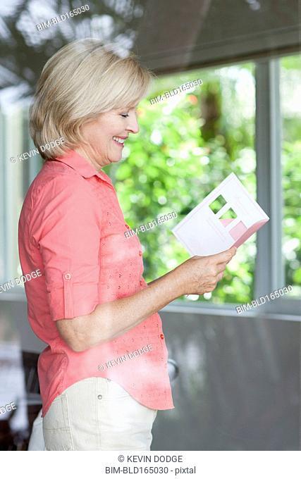 Smiling Caucasian woman reading card