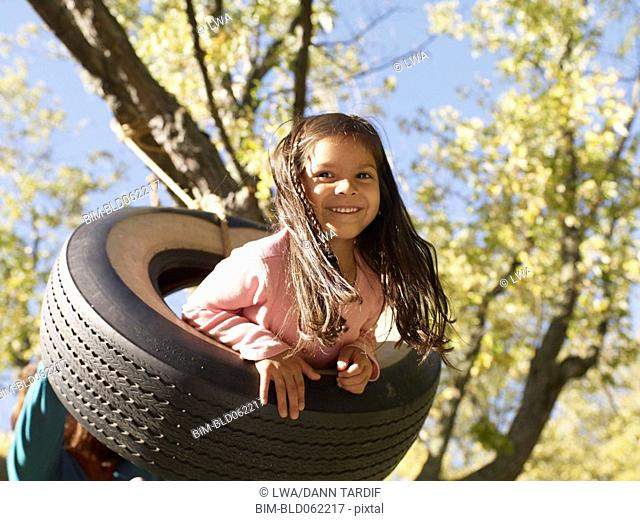Hispanic girl swinging on tire swing
