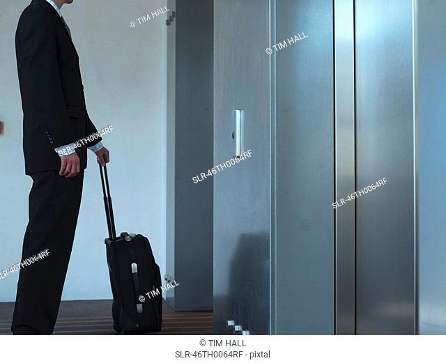 Businessman with luggage at elevator