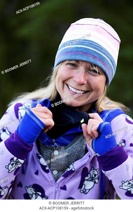 An colorfully dressed female camper shares a laugh as she describes her many layers of outer wear while camping at Bedwell Lake, Strathcona Park