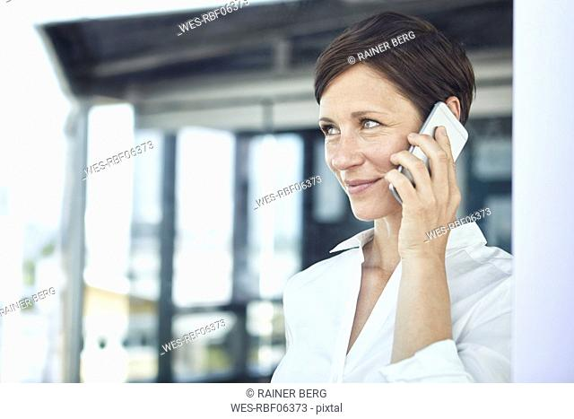 Portrait of smiling businesswoman on cell phone