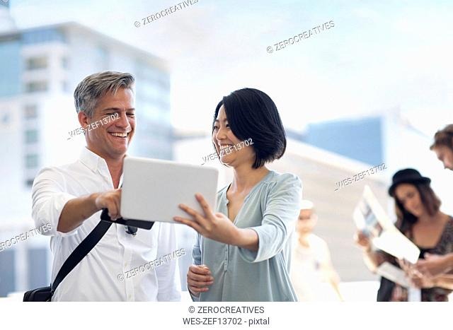 Group of happy casual businesspeople sharing tablet on urban square