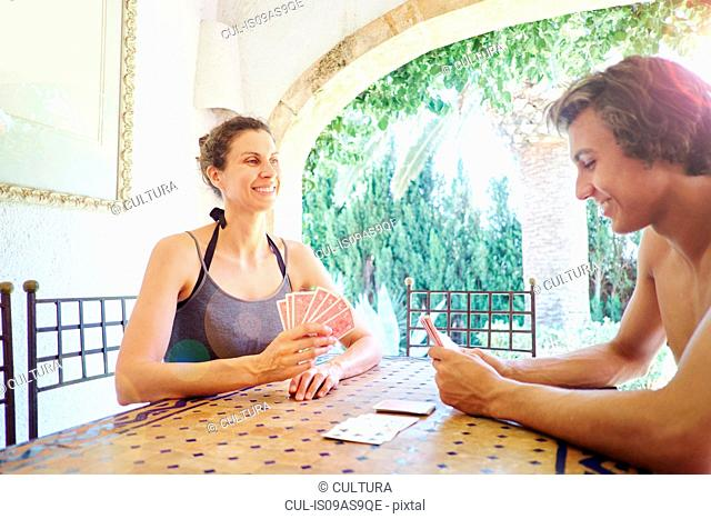 Mature woman and son playing cards at patio table