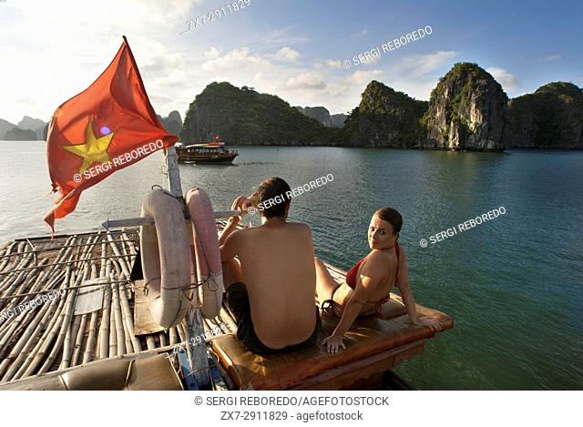 Romatic couple inside a Chinese Junk, Halong Bay Tourist Boat Tour, Vietnam. Junk, boat sailing amongst karst limestone mountains at Cat Ba National Park