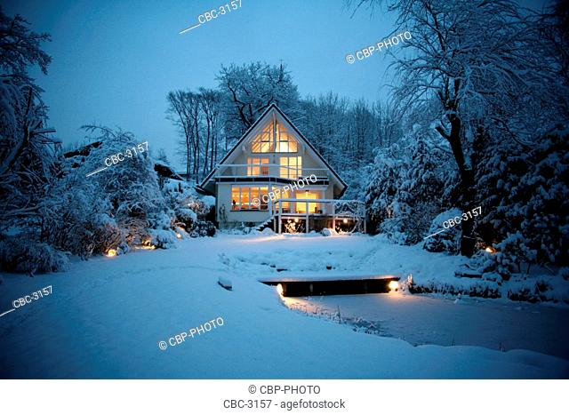 Exterior View Of A House, Illuminated, In Snow