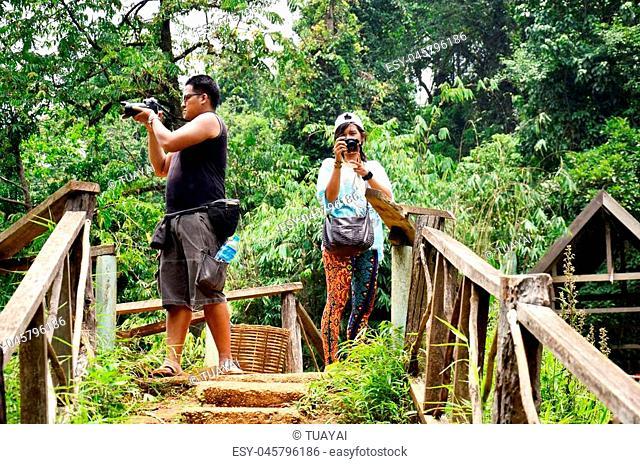 Travellers man and woman people look and shooting photo Tad Yeuang waterfall at viewpoint in Bolaven Plateau at Paksong, Champasak, Laos