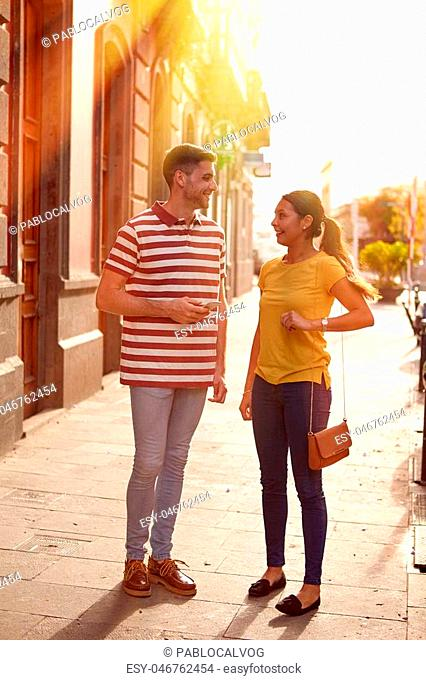 Young couple looking at each other talking happily while facing each other dressed casually in t-shirts with old buildings behind them