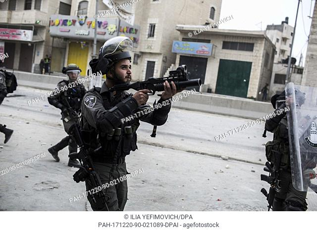 An Israeli armed soldier aims a tear gas launcher run towards Palestinian protesters during clashes following protests against US President Donald Trump's...