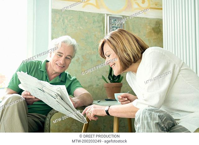 Couple reading newspaper together, smiling