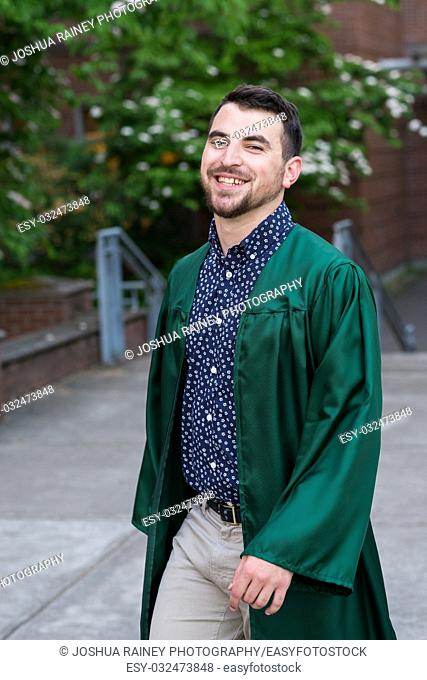 Male model wearing a graduation gown on campus at a university in Oregon