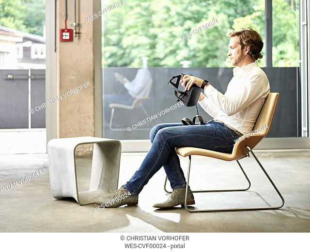 Man holding VR glasses sitting on chair