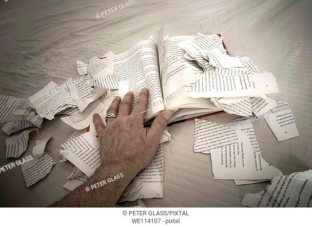 Man's hand on a book with ripped-up pages