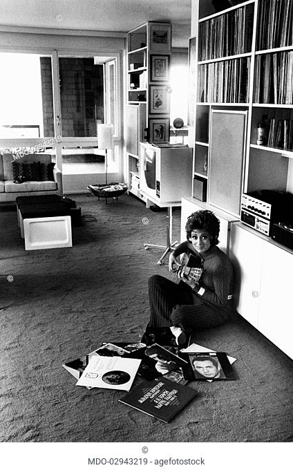 Italian singer, actress and showgirl Caterina Valente playing guitar in the livingroom at home. Arosio, 1970