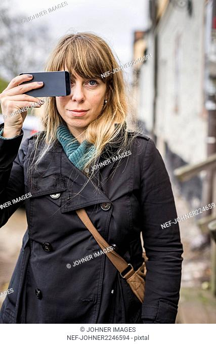 Young blond woman holding cell phone in front of face