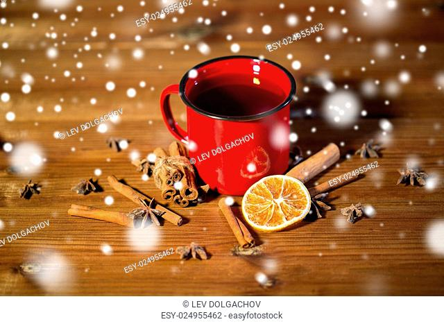 christmas, holidays, cooking and spice concept - close up of tea cup with cinnamon, anise and dried orange on wooden table from top