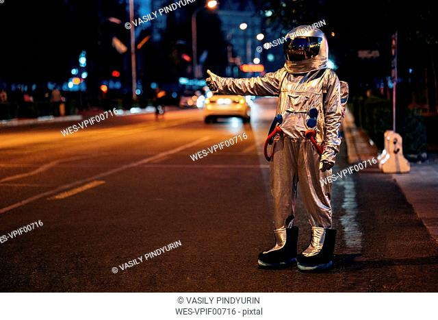 Spaceman standing on a street in the city at night hitchhiking