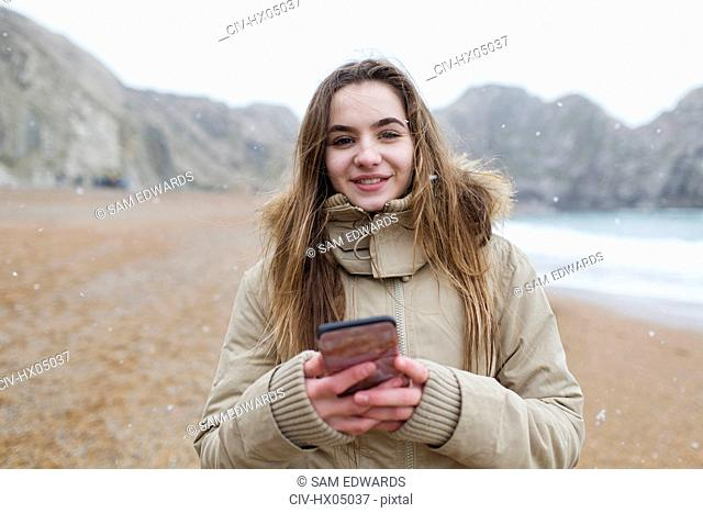 Portrait smiling teenage girl texting with smart phone on snowy winter beach