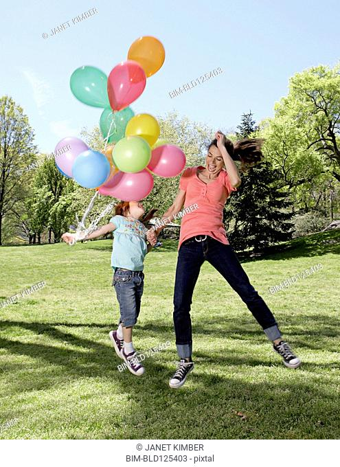 Mixed race mother and daughter holding balloons in park