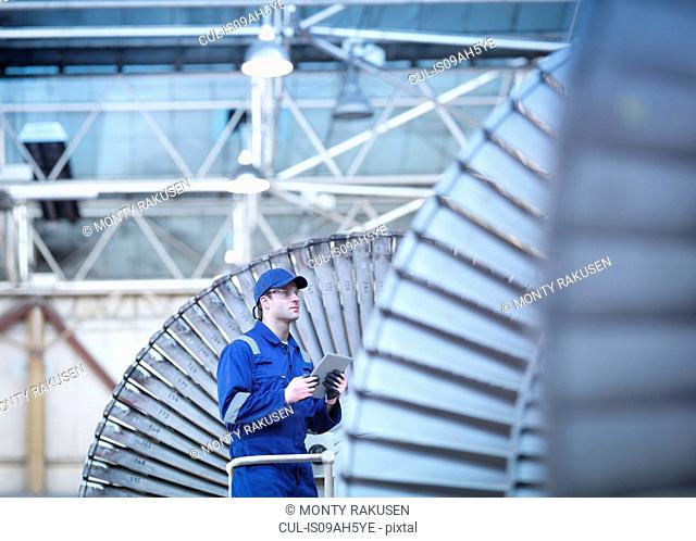 Engineer inspecting steam turbine in repair bay