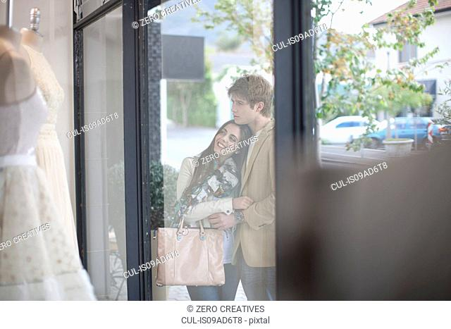 Young couple window shopping, looking through shop front