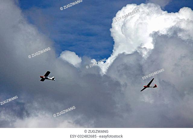 An aeroplane towing a glider aircraft up into a blue cloudy sky