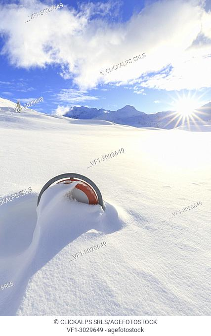 The setting sun illuminates a road sign submerged in the snow. Simplon Pass, Canton of Valais/Wallis, Switzerland