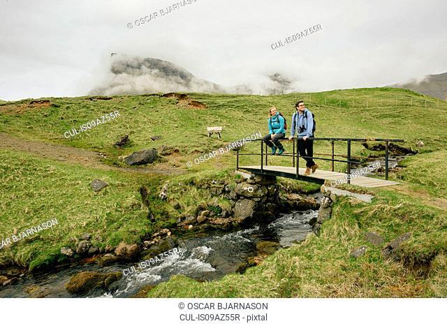 Hikers enjoying view on bridge above stream, Gasadalur, Vagar, Faroe Islands