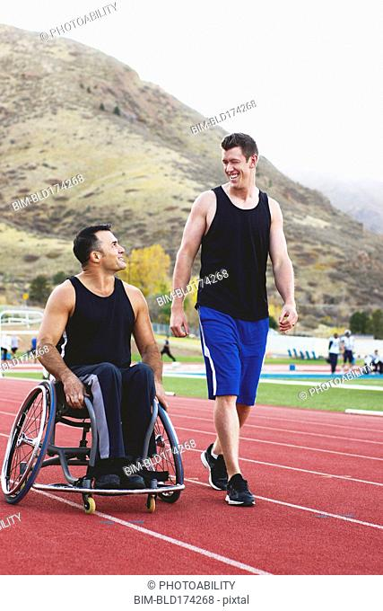 Paraplegic athlete in wheelchair with friend on track