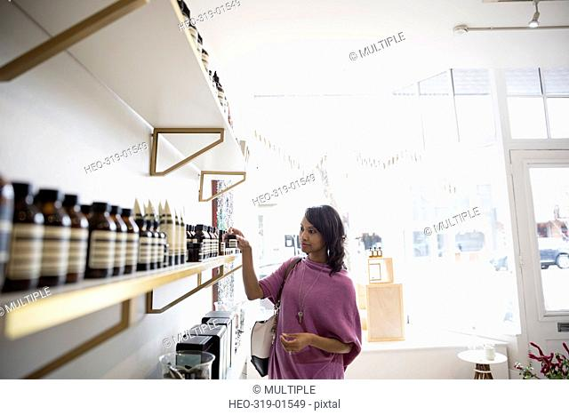 Woman shopping browsing merchandise on shelves in home fragrances shop