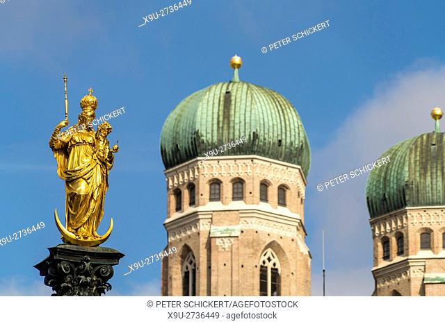 Virgin Mary atop the Mariensäule and the church towers of the Frauenkirche in Munich, Bavaria, Germany