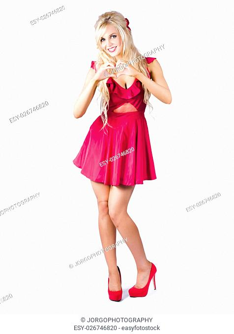 Beautiful young blond woman in short dress making love heart shape with hands, white background