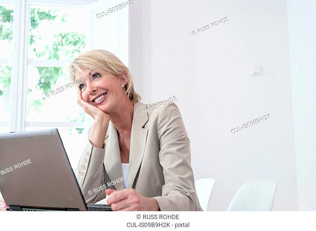 Business woman, hand on chin looking away smiling