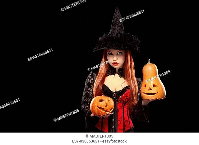 Girl in witch costume with two Halloween pumpkin isolated on black background