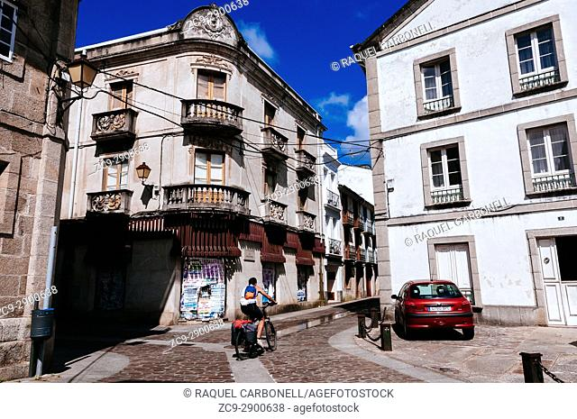 Young cycling tourist riding bicycle on cobbled street among traditional buildings, Mondoñedo, Lugo, Galicia, Spain