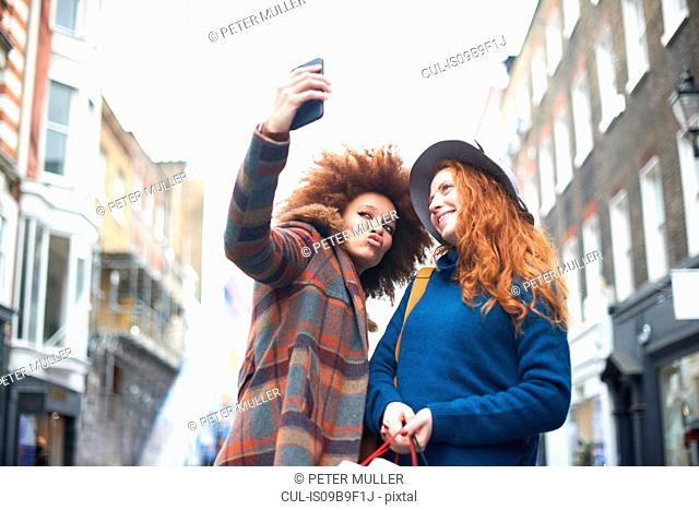 Two young women in street, taking selfie, using smartphone, low angle view